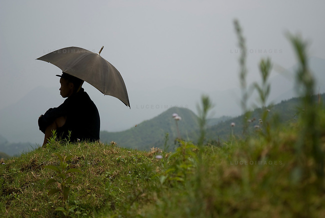 A man shades himself in a minority village outside of Sapa, Vietnam.