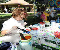 STAFF PHOTO ANDY SHUPE - Faye Wiest, 5, of Fayetteville decorates a tie-dyed T-shirt during the All Children's Fair: Welcoming Feet in Motion Sunday, Sept. 21, 2014, at Walker Park in Fayetteville. The event was organized by the Coalition to Stand With All the Children as a way to raise money for and awareness of refugee children at the U.S. boarder with Mexico.