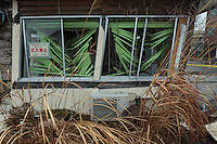 Earthquake damaged building being overrun with vegetation inside the Fukushima exclusion zone, Namie, Fukushima, Japan. Wednesday March 9th 2016. The Great East Japan Earthquake on March 11th 2011 was followed by a massive tsunami that levelled much of the Tohoku coast in north east Japan, killing around 18,000 people and causing meltdowns and explosions at the Fukushima Daiichi nuclear power station leading to the contamination and evacuation of a 20 kilometre exclusion zone around the plant.
