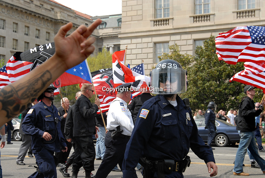 "April 19, 23008. The National Socialist Movement held a rally and march against illegal Immigration in Washington DC. Hundreds of police officers wearing riot gear walked down Constitution Ave. escorting the group.  The NSM walked.towards the Capitol waving swastika flags and shouting ""Sieg Heil"".  Several.counter protesters clashed with the group and were arrested"