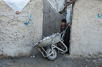 The Chamne Babrak refugee camp in Kabul 5-1-14 A boy removes mud from his home with a wheelbarrow.