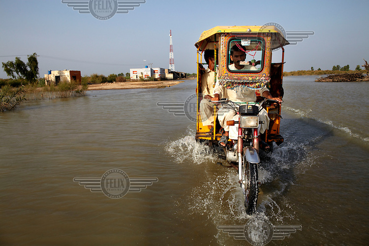 A rickshaw travels along a flooded road near Sukkur. Severe flooding had left at least 1,600 people dead and affected up to 20 million.