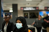 A Dulles International Airport worker assists passengers as they arrive from Dubai after a 14-hour flight on Emirates flight 231, at the international terminal at Dulles International Airport in Dulles, Va., Monday, March16, 2020. Some people are taking the precaution of wearing face masks as they arrive to be greeted by family and or friends. Credit: Rod Lamkey / CNP