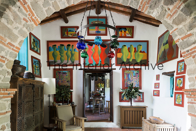 The sitting room with stone and tile arch and paintings by South African artist Nicolaas Maritz. Traditional local materials were kept during the restoration of the house, such as the terracotta tiles on the floor and ceilings and the original massive wooden beams.