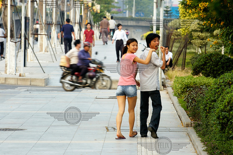 A young couple walk down the street.