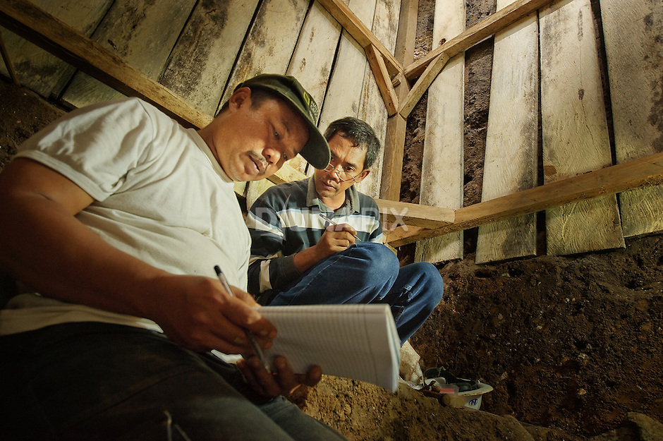 Lead researchers Thomas Sutikna and Wahyu Saptomo compare notes inside an excavation pit at Liang Bua cave, discovery site of the Flores hobbit, Homo floresiensis