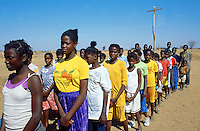 Angola. Cuando Cubango. Mavinga. Catholic church. Religious service on sunday morning. A column of boys and girls wait outside the church before the start of the mass.  Holy cross. © 2002 Didier Ruef