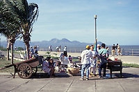 People relaxing on the Malecon lakeside walkway in Managua, Nicaragua. Lake Nicaragua and volcanoes in background.