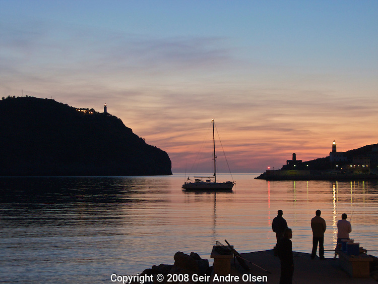 People fishing in the beautiful sunset in the harbour of Port Soller, Majorca, Spain
