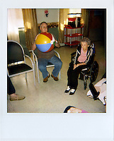 Mike Eberspecher throws a beach ball with other Alzheimer's patients at the Douglas Care Center.  ..Alzheimers.  Douglas, Wyoming..Mike Eberspecher was diagnosed at 60 with early onset Alzheimers.  The disease, a subset of dimentia, gradually impairs the brain's ability to form new memories, simultaneously undoing connections that make up old memories.  Patients generally experience memory loss from the present, backwards.  Early onset Alzheimers tends to progress quicker in younger patients. ..Carolyn Eberspecher has been caring for her husband, Mike, for the last five years.  Over time, he has gradually lost his ability to care for himself and relies on her for most of his needs.  In April of 2010, Carolyn will place her husband in an Alzheimer's care unit in the town's nursing home.  .Carolyn Eberspecher attends church in Douglas, Wyoming.  Carolyn and Mike attend separate churches.  After Mike was diagnosed with Alzheimers, he returned to attending Mormon church, a tradition which had fallen by the wayside for most of his adult life.