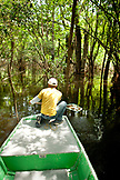 BRAZIL, Agua Boa, fishing guide maneuvering a boat through the mangroves, Agua Boa River and resort