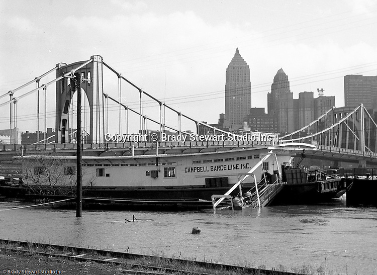 Pittsburgh PA:  View of the high water from the Allegheny River near River Avenue and the 6th Street Bridge on the North Side - 1959. Men boarding a Campbell Bargeline barge to make sure it was secure.