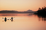 San Juan Islands, Sea kayakers paddle into sunrise, the San Juan Islands and Mount Baker in the distance, Little D'Arcy Island,