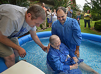 STAFF PHOTO BEN GOFF  @NWABenGoff -- 09/06/14 Chuck Mills, left, of Huntsville, helps Victor Caballeros of Siloam Springs baptize resident Mary Carte in a small pool following a worship service for residents and staff at Ashley Health & Rehabilitation Center in Rogers on Saturday September 6, 2014.