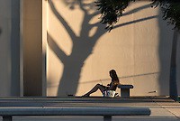 As the sun sets and casts shadows from trees onto Herrick Chapel, a student studies next to the Gilman Fountain on the campus of Occidental College, Oct. 21, 2016.<br />