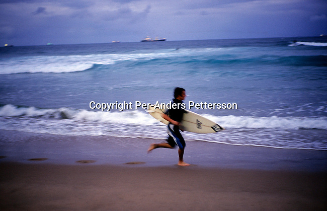 DURBAN, SOUTH AFRICA - JANUARY 2: A surfer runs along the beach as the sun sets on January 2, 2004 in Durban in Natal Province, South Africa. Durban is a popular tourist destination along the Indian Ocean and locals and tourists enjoy the beach on the weekends. .(Photo: Per-Anders Pettersson/Getty Images).....