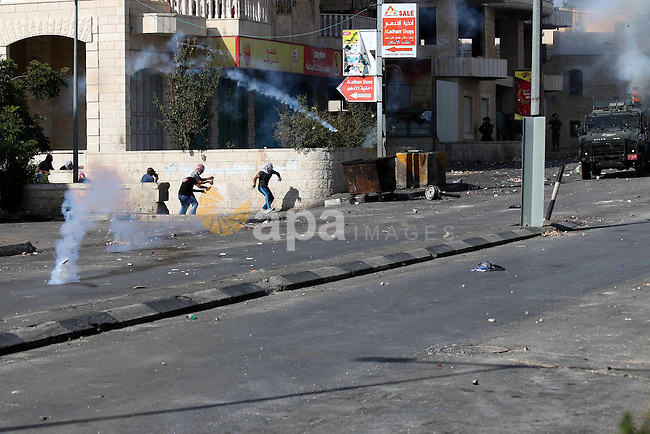 Palestinian protesters throw stones at Israeli troops during clashes in the West Bank city of Bethlehem October 14, 2015. Seven Israelis and 30 Palestinians, including children and assailants, have been killed in two weeks of bloodshed in Israel, Jerusalem and the occupied West Bank. The violence has been partly triggered by Palestinians' anger over what they see as increased Jewish encroachment on Jerusalem's Al-Aqsa mosque compound. Photo by Muhesen Amren