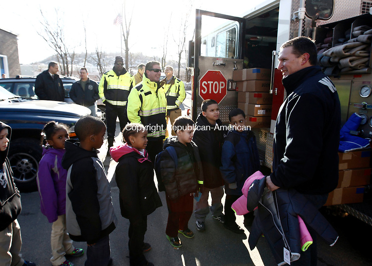 """Waterbury, CT- 28 February 2014-022814CM01-  Members from the Waterbury Fire Fighters Association Local 1339, including executive board member Lt. Patrick Maloney, at right, donate coats to children at the Boys and Girls Club of Greater Waterbury on Friday.  The group was partnering with Operation Warm and the International Association of Fire Fighters  for the """"Firefighters coats for Kids Foundation"""", which provide Made in the USA winter coats for children.     Christopher Massa Republican-American"""