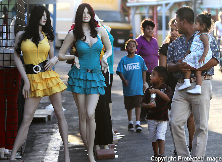 Women's clothing is displayed on mannequins as a family walks by at the Escondido Swap Meet in 2010.  photo for the North County Times
