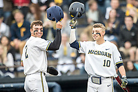 Michigan Wolverines outfielder Jonathan Engelmann (2) is greeted at the plate by teammate Blake Nelson (10) after scoring against the Maryland Terrapins on April 13, 2018 in a Big Ten NCAA baseball game at Ray Fisher Stadium in Ann Arbor, Michigan. Michigan defeated Maryland 10-4. (Andrew Woolley/Four Seam Images)