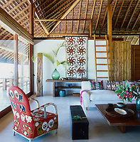 The living room has a polished concrete floor, beaded African chair and antique suzani used as a wall hanging