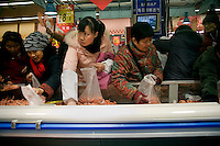 Shoppers seek out discount meat at RT Mart, a hypermarket in Nanjing, Jiangsu, China.