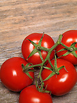 Ripe cluster tomatoes on on rustic wood background