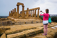 Agrigento, tourist taking a photo at Temple of Juno, Valley of the Temples (Valle dei Templi), Sicily, Italy, Europe. This is a photo of a tourist taking a photo at The Temple of Juno (Tempio di Giunone) at The Valley of the Temples (Valle dei Templi), Agrigento, Sicily, Italy, Europe.