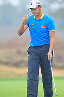 Cao Yi (CHN) sinks his putt on the 14th green during Friday's Round 2 of the 2014 BMW Masters held at Lake Malaren, Shanghai, China 31st October 2014.<br /> Picture: Eoin Clarke www.golffile.ie