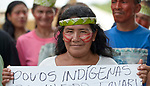 A woman holds a sign as indigenous people march through the streets of Atalaia do Norte in Brazil's Amazon region on March 27, 2019, protesting a central government plan to turn control of health care over to municipalities, in effect destroying a federal program of indigenous health care. Indian rights activists are worried that the government of President Jair Bolsonaro is reducing or eliminating protections for the country's indigenous people.