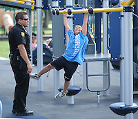 NWA Democrat-Gazette/ANDY SHUPE<br /> Officer Eric Cardenas with the Springdale Police Department smiles Thursday, Sept. 10, 2015, as he plays with Oscar Baires, 9, a fourth-grader at Jones Elementary School in Springdale, during a dedication ceremony for the Kiwanis International Centennial Playground at the renovated Luther George Grove Street Park in Springdale. The playground comes as a part of Kiwanis' national effort to build playgrounds to mark the organization's 100-year anniversary.