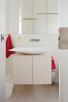 A shallow dish-shaped wash basin heralds the entrance to this contemporary bathroom which is lined with floor-to-ceiling white cupboards