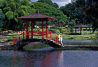 Two young girls crossing over a pagoda bridge at  Liliuokalani park  in Hilo town on the Big Island of Hawaii
