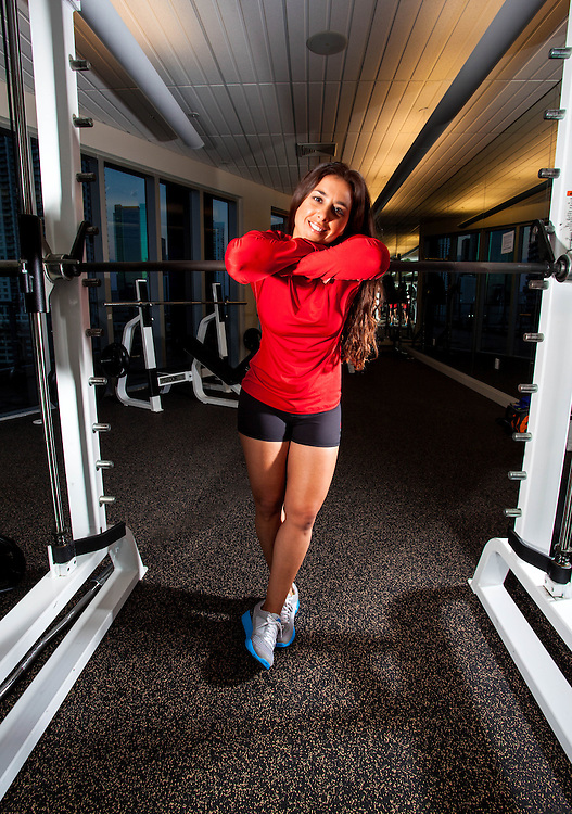 young brunette woman exercising and stretching in a gym