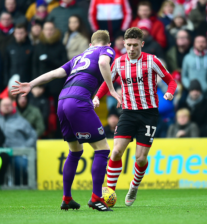 Lincoln City's Shay McCartan runs at Grimsby Town's Alex Whitmore<br /> <br /> Photographer Andrew Vaughan/CameraSport<br /> <br /> The EFL Sky Bet League Two - Lincoln City v Grimsby Town - Saturday 19 January 2019 - Sincil Bank - Lincoln<br /> <br /> World Copyright &copy; 2019 CameraSport. All rights reserved. 43 Linden Ave. Countesthorpe. Leicester. England. LE8 5PG - Tel: +44 (0) 116 277 4147 - admin@camerasport.com - www.camerasport.com