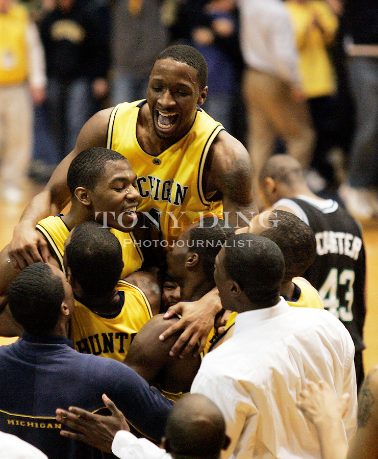 Michigan guard Dion Harris (center left) is congratulated by teammates, including guard Daniel Horton (top), after Michigan overcame Notre Dame in triple overtime 87-84 in a second-round NIT basketball game on Monday, March 20, 2006, in Ann Arbor, Mich. (AP Photo/Tony Ding)