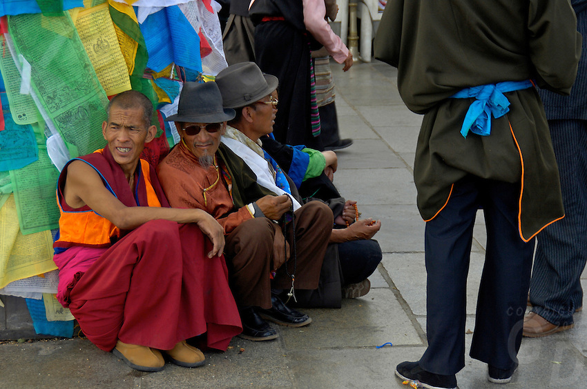 Tibetean gather just outside the Jokhang Temple,.The Jokhang Temple is one of Tibet's holiest shrines, originally built in 647 A.D. in celebration of the marriage of the Tang Princess Wencheng and the Tubo King Songtsen Gampo. In front of the gate is a stone Tablet of Unity from the Tang Dynasty; inscribed are both Chinese characters and Tibetan script. Nearby is the stump of the willow tree said to have been planted by Princess Wencheng herself; two younger willow trees now flank the stump of the first tree...Located in the center of old Lhasa, the temple was built by craftsmen from Tibet, China, and Nepal and thus features different architectural styles. The temple is also the spiritual center of Tibet and the holiest destination for all Tibetan Buddhist pilgrims. In the central hall is the Jokhang's oldest and most precious object--a gold statue of a seated 12-year-old Sakyamuni. This is said to have been transported to Tibet by Princess Wencheng from her home in Changan in 700 A.D. Other precious antiques in the temple include a silk portrait of Buddha from the Tang Dynasty and a pearl gown and gold lamp from the Ming Dynasty. The three-leafed roof of the Jokhang offers splendid views of the bustling Barkhor market and across to the Potala Palace..