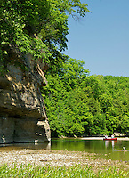 Canoeists paddling down Sugar Creek mid-May under a blue sky in Turkey Run State Park, Indiana, USA