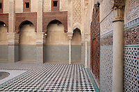 The Al-Attarine Madrasa, a religious school built 1323-25 by the Marinid Sultan Uthman II Abu Said, who ruled 1310-31, in the medina of Fes, Fes-Boulemane, Northern Morocco. This courtyard has a central marble fountain, a zellige tiled floor and lower walls and intricate carved stucco and wooden walls with horseshoe arches and pillars. The medina of Fes was listed as a UNESCO World Heritage Site in 1981. Picture by Manuel Cohen