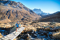 Trail running across a bridge above Val Funtauna between Berguns and Davos, Switzerland with golden fall colors