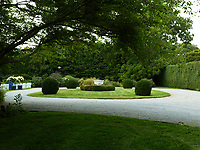 The in-out drive is set around a circular area of lawn planted with shrubs.