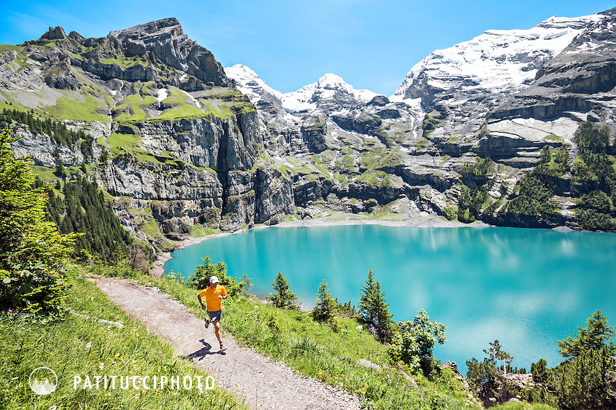 Trail running around the turquoise lake of the Oeschinensee, above Kandersteg, Switzerland. The round the lake trail is a very exposed path with cables in many places to hold on to.