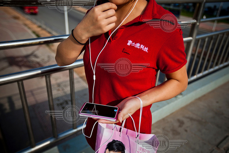 A Foxconn employee uses a unbranded smartphone as she leaves the factory for home. Foxconn is a Taiwanese technology company that makes products for Apple and Sony among others and is the largest private sector employer in China.