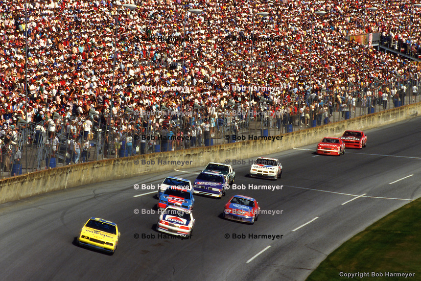 DAYTONA BEACH, FL - FEBRUARY 15: Dale Earnhardt drives his Wrangler Chevrolet ahead of a group of cars during the Daytona 500 on February 15, 1987, at the Daytona International Speedway in Daytona Beach, Florida.