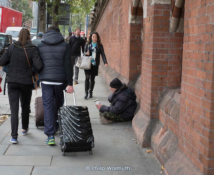 A homeless man begging on a street in Kings Cross London