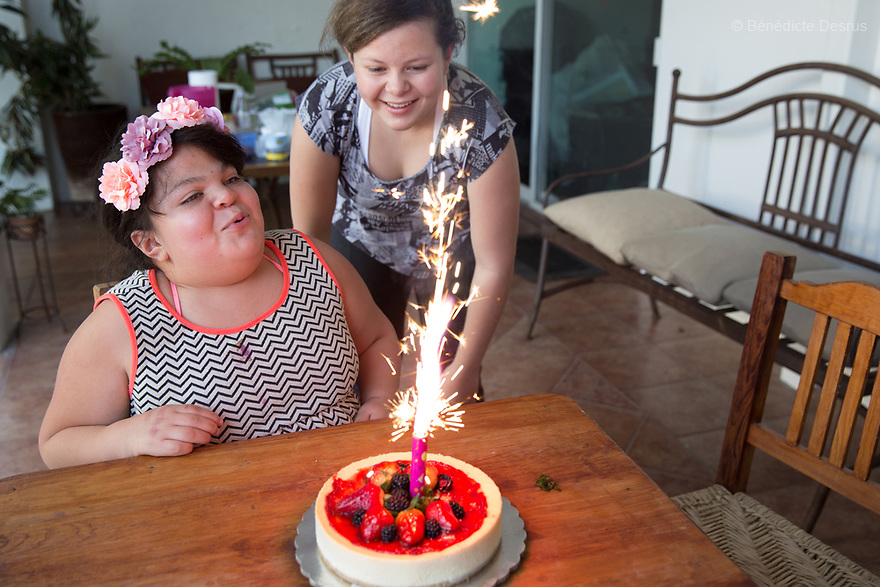"""Ana Ximena Navarro (L) and her sister Ana Yamila Navarro (R), are pictured at their home in Guadalajara, Mexico on February 22, 2017. Ximena was diagnosed as an infant with Hurler syndrome. Hurler syndrome is the most severe form of mucopolysaccharidosis type 1 (MPS1), a rare lysosomal storage disease, characterized by skeletal abnormalities, cognitive impairment, heart disease, respiratory problems, enlarged liver and spleen, characteristic facies and reduced life expectancy. Ximena was being given enzyme replacement therapy (ERT) when she was 19 months old, and she was suddenly able to eat and sleep. She is now 12, and has normal hormonal development for her age, although some mental delay, according to her father. """"Without the treatment, she would have died from all the complications — untreated, children have a very bad quality of life and typically die before they are seven"""", her father says. Photo credit: Bénédicte Desrus"""