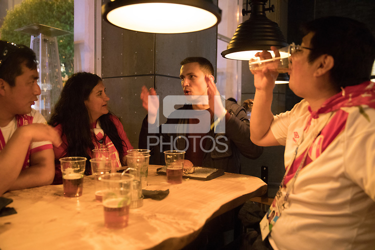 YEKATERINBURG, RUSSIA - June 21, 2018: A Russia fan talks with Peru fans in a restaurant after their lost their 2018 FIFA World Cup group stage match against France at Yekaterinburg Arena Stadium. Many Russian fans enjoyed the warmth and friendliness of the Peru fans despite their loss.