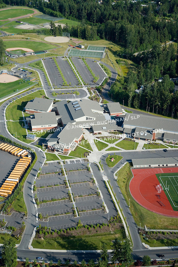 Aerial view of a large, suburban, public high school in Bonney Lake, Washington with yellow school buses defining the edge of the property and a red running track providing contrast