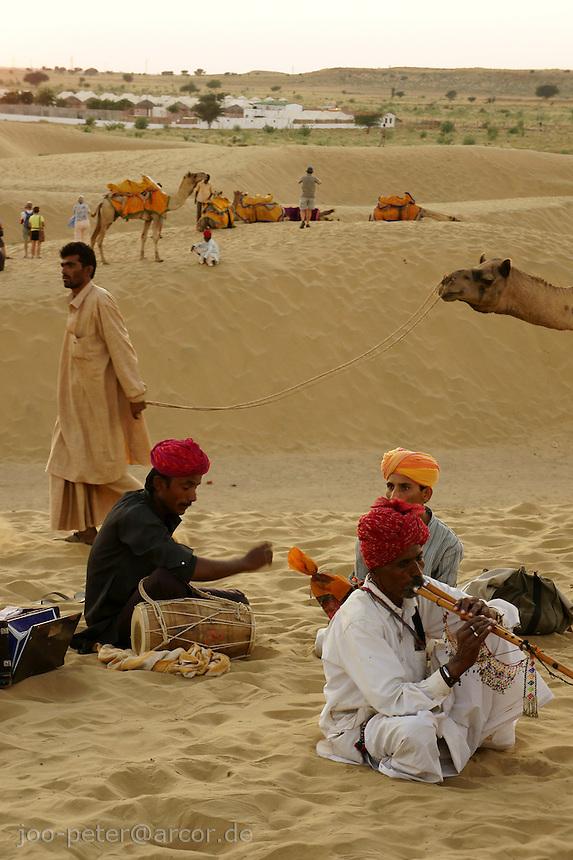 camel guides resting in desert dunes at sunset time