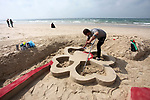 """Palestinian artist Mohammed Totah with amputated leg, paints a sand sculpture reads in Arabic """"my mother"""" to mark the Mother's Day, at the beach of Gaza city on March 21, 2019. Totah, 31 year-old, who had lost his leg during the Israeli war on Gaza Strip in 2008, despite his disability, he succeeded in writing and drawing sculptures by sand on the Gaza beach marking the national events. Photo by Mahmoud Ajjour"""